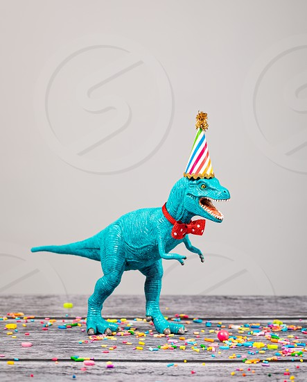 Toy dinosaur at a Birthday party wearing a hat and bow tie. photo