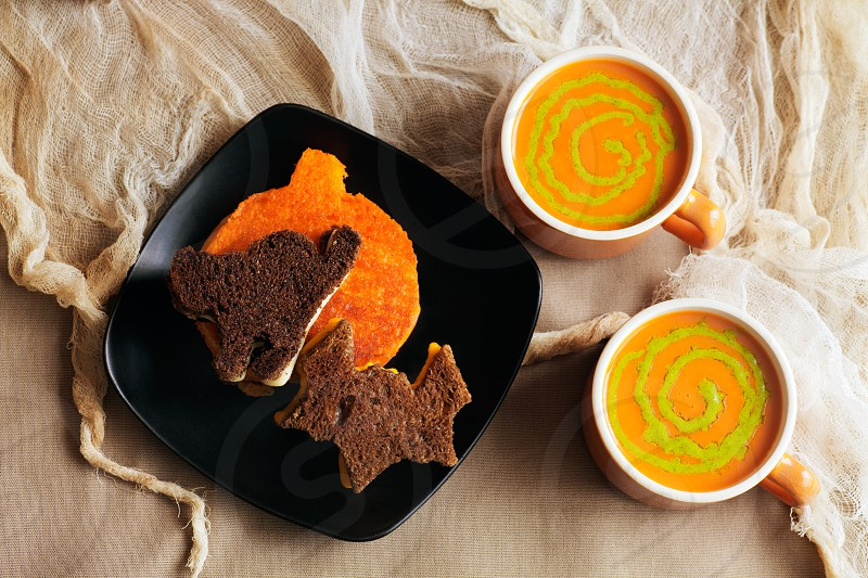 Hot cup of soup: tomato with pesto swirls and grilled cheese sandwiches of various Halloween shapes.  photo