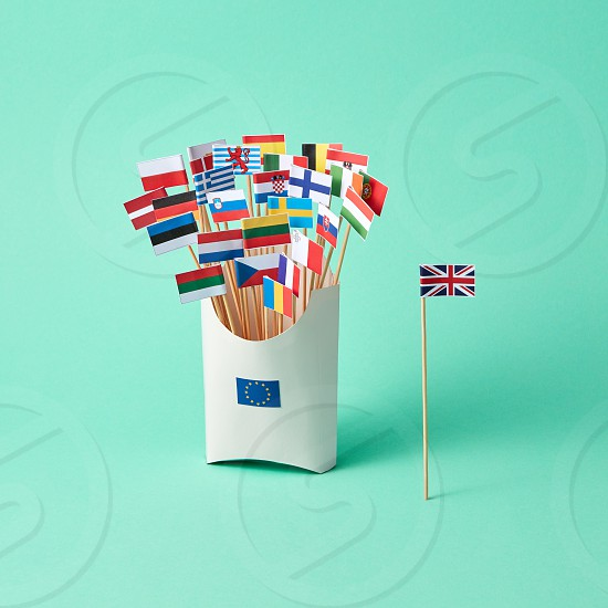 Different paper flags in a cardboard box with an EU sign and the flag of Britain aside on a green background . The exit of Britain from the EU photo