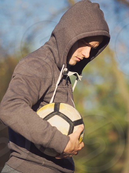 Soccer Player Posing with Football in the Park on a Sunny Autumn Day photo