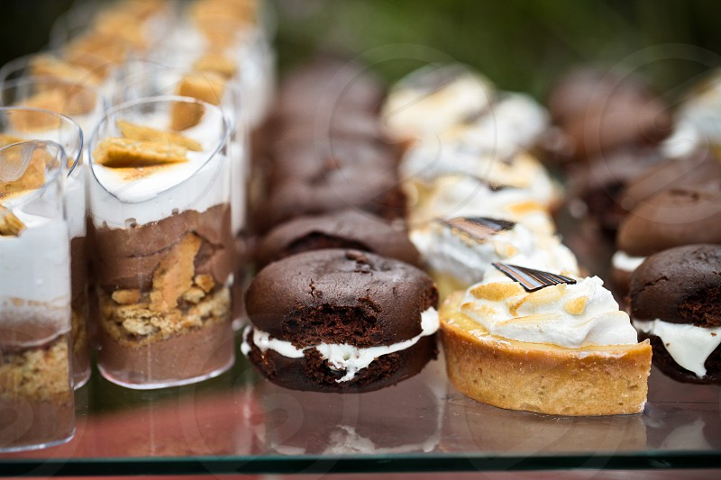 Food culinary dining snacks treats eats. Desserts chocolate tarts petit fores vanilla icing frosting lemon graham smores marshmallow. photo