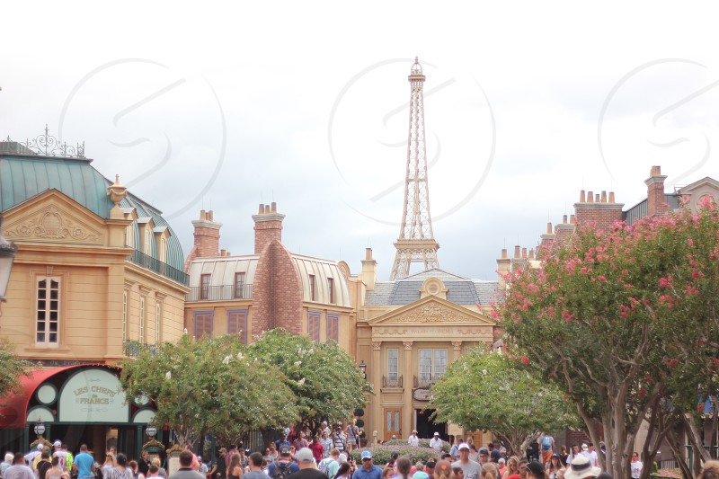 group of people walking between the buildings in front of tower during daytime photo