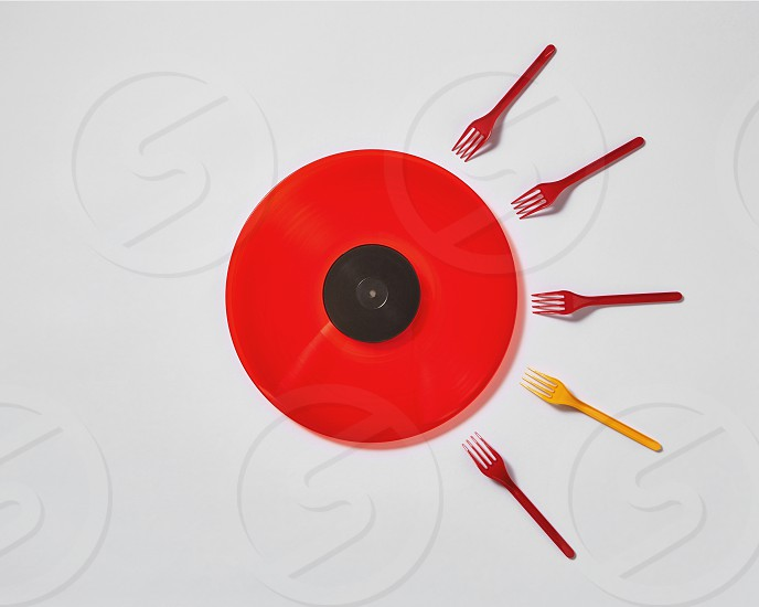 Creative composition with red vinyl record and plastic colored forks on a gray background. Concept of fertilized egg by sperms. photo