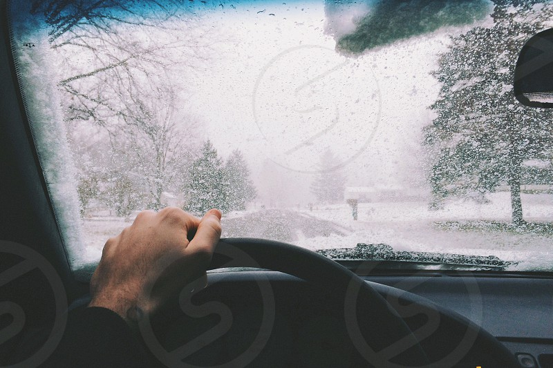 person driving vehicle while snowing during daytime photo