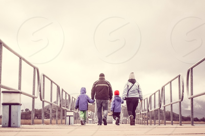 Family On Winter Vacation Walking Across A Bridge Holding Hands photo