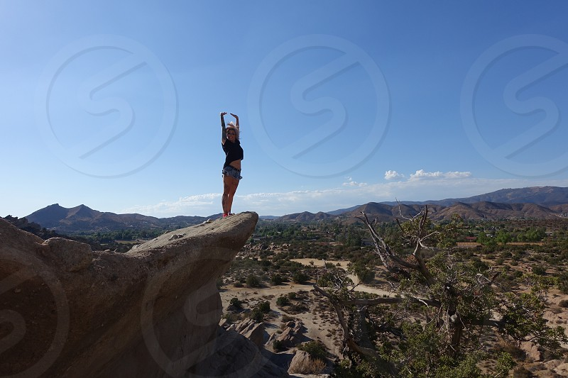 Woman standing on a rick formation at Vazquez Rocks near Palmdale california with her arms stretched out overhead  photo