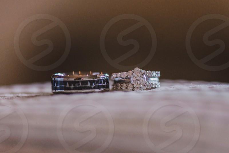 White gold wedding rings with diamonds on white pillow photo