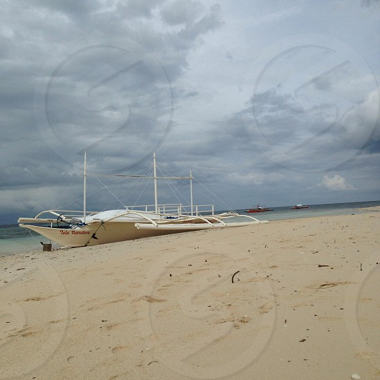 white speed boat on seashore photo