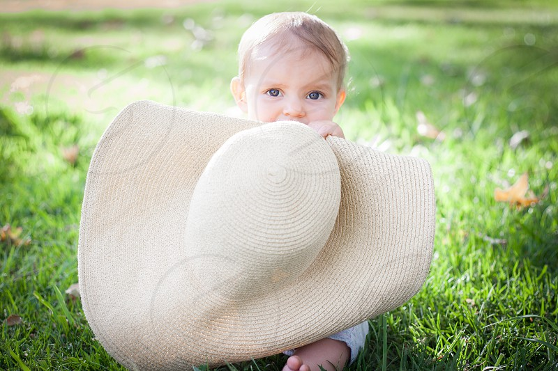 baby holding brown hat photo