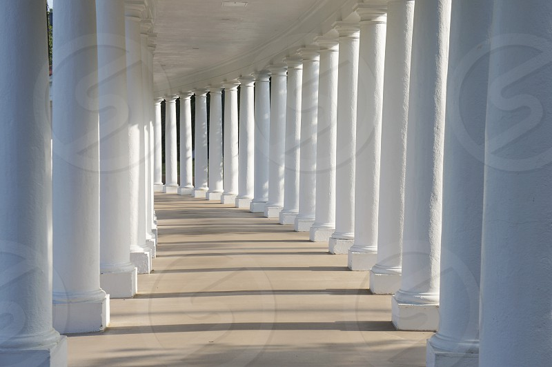 View down a walkway surrounded by white columns photo