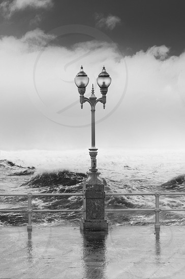 2 shade street lamp post with strong sea waves in the background in grayscale photography photo