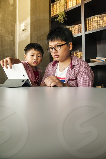 Kids using mobile device in a library photo