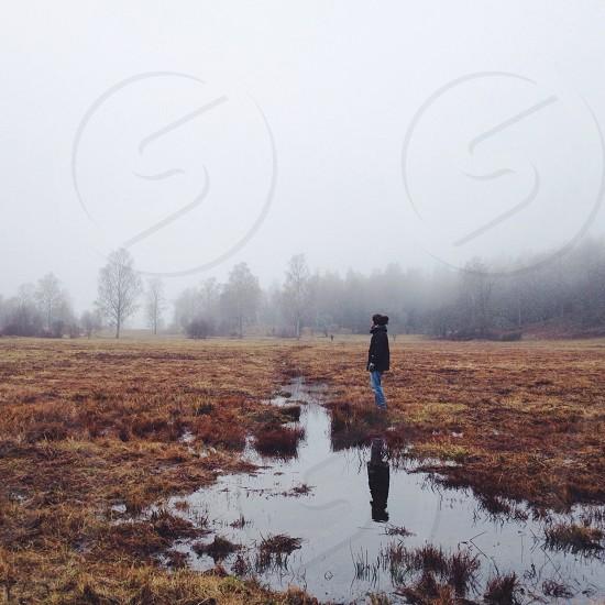 woman standing wearing black jacket in the brown field photo