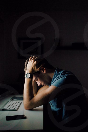 man head down on desk in green shirt with watch photo