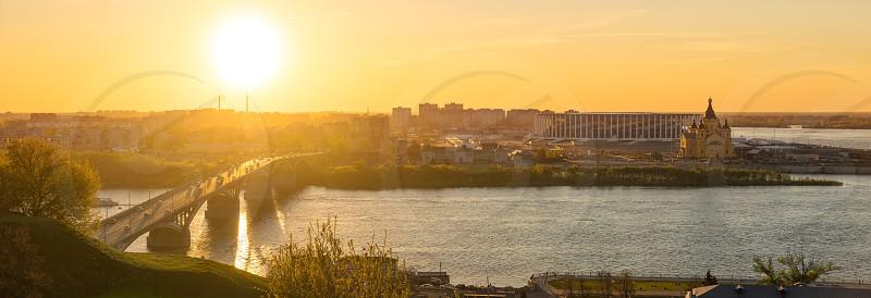 Panorama of Nizhny Novgorod city Kanavinsky Bridge Oka River Alexander Nevsky Cathedral riverbank and stadium at golden hour sunset time in summer photo