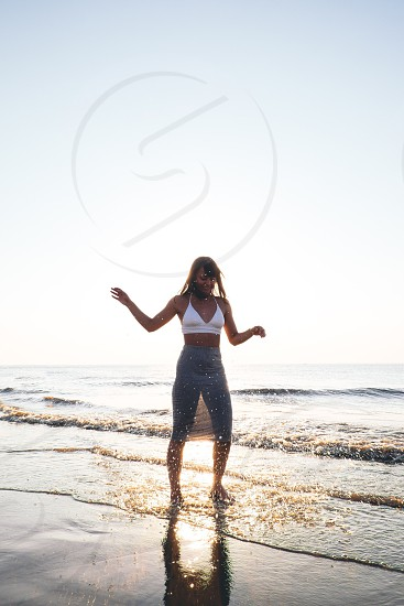 woman in white halter crop top and gray sheer skirt standing on the shore under yellow and blue sky photo