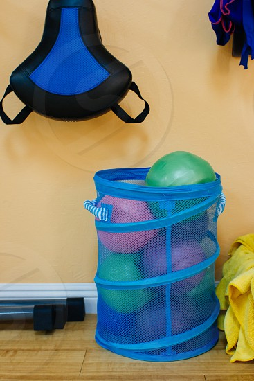 green pink and purple ball on blue round basket beside yellow painted wall with black and blue bicycle seat photo