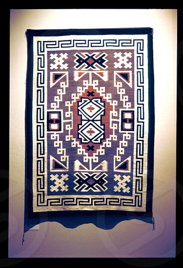 Navajo woolen blanket with bright colored geometric designs typical of the Navajo. Women spin the wool from sheep dye the threads with vegetable dyes and then weave them on a loom. Navajo rug are used as blankets and wall hangings. photo