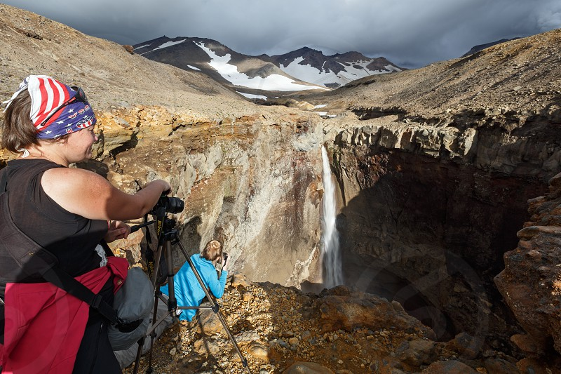 MUTNOVSKY VOLCANO KAMCHATKA PENINSULA RUSSIA - SEP 8 2015: Young women tourists photographers takes picture of waterfall on mountain river in Dangerous Canyon with rocky slope on active volcano Mutnovskaya Sopka. photo