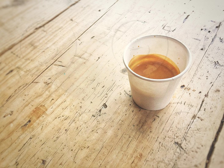 Disposable recycled paper cup with coffee on a wooden table on a sunny day photo