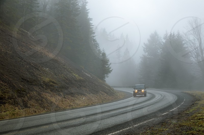 Car comes around the bend in heavy fog photo