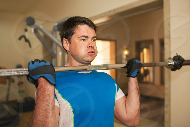 Young man doing strengthen exercise in the gym. He lifting barbell without weight disks photo