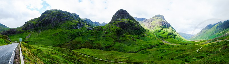 Panoramic of a mountain road in Glencoe the highlands of Scotland with clouds and green landscape and mountains photo
