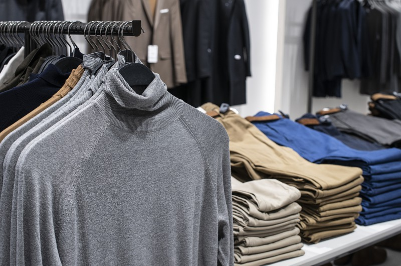 Blouses and jeans on shelf in fashion clothing store. Casual clothes in shop. Commercial and fashion concept.  photo