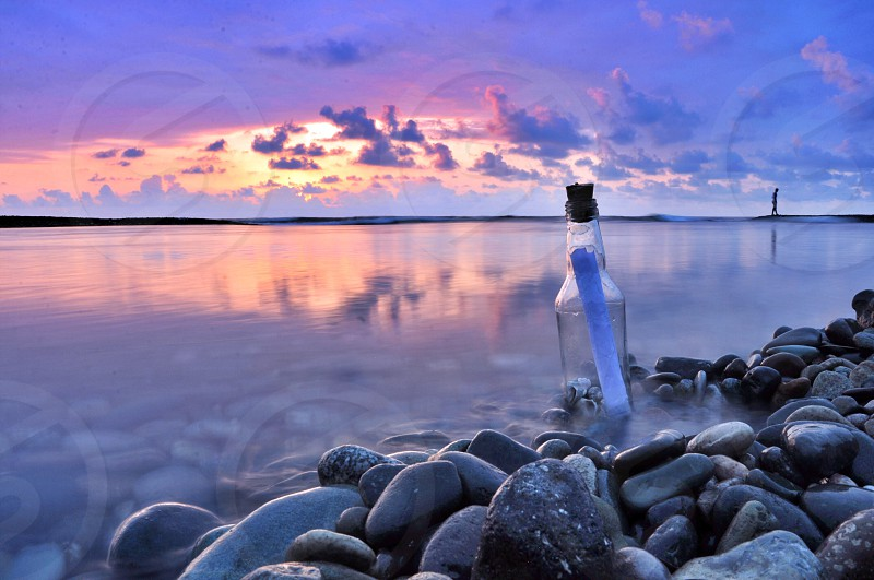 note in clear glass bottle with cork standing straight on rocky ocean shoreline under pink and purple cloudy sky at sunset photo