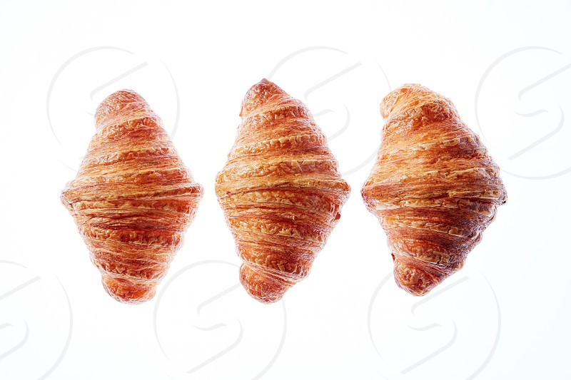 Freshly baked tasty pastry. Pattern of three french fresh croissants on a white background. Place for text. Close up view. photo