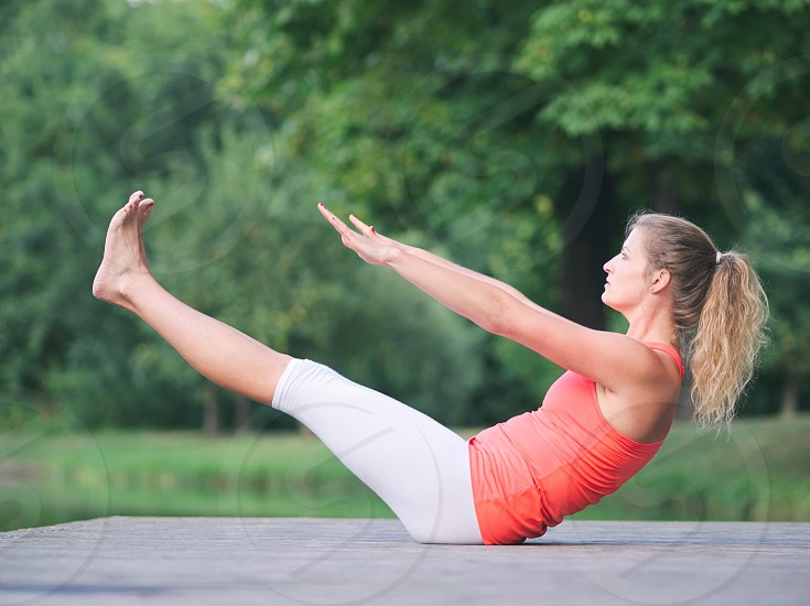 Woman in her Thirties Doing Yoga in the Park on a Pier photo