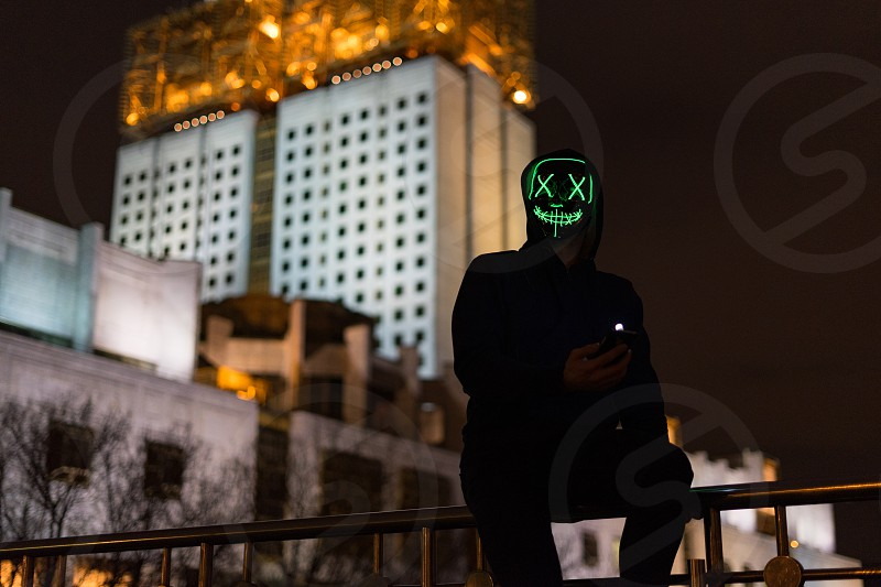 Male adult in green led mask silhouette in front of lit high building photo