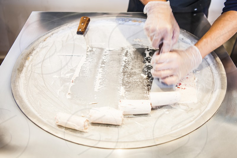 man wearing clear gloves cutting white dough on top of stainless steel round shape container photo