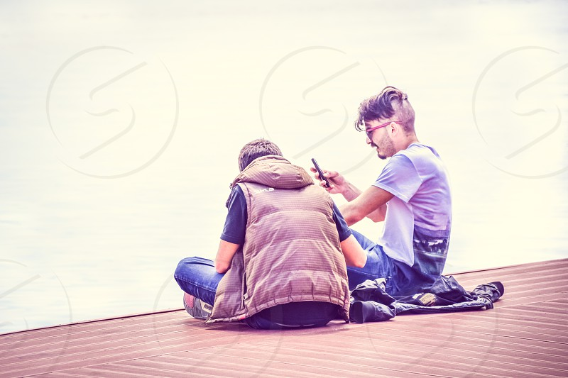Young People Teenagers Sitiing On The Dock And Checking Mobile Phones photo