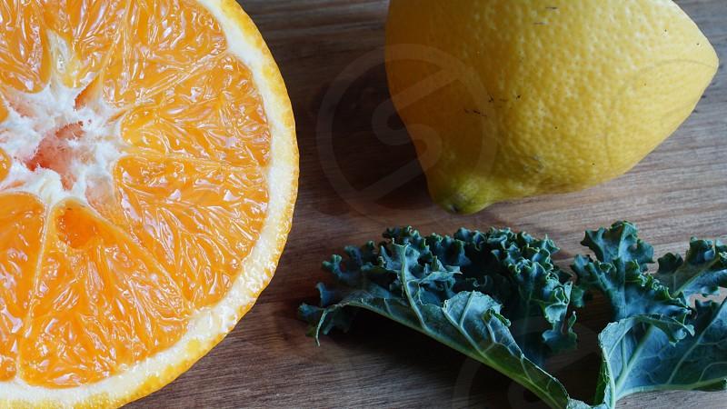 sliced orange and sliced lemon near green leafy vegetable photo
