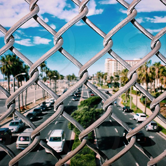 chain link fence against road with row of cars parked under blue sky photo