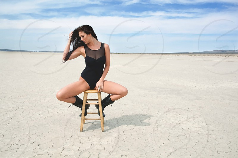 woman in black sitting on a stool photo
