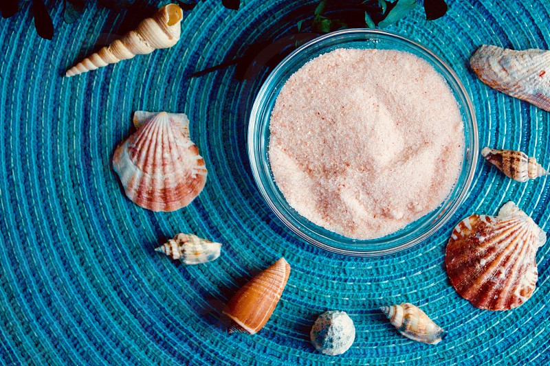 Flat lay of Himalayan pink salt and seashells  on a turquoise surface photo