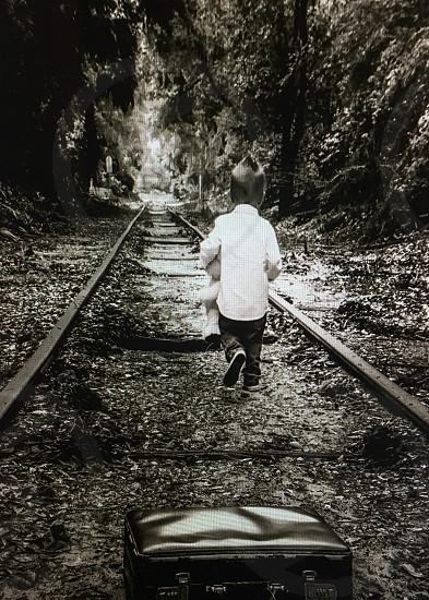 Black and white rails train tracks boy traveling photo
