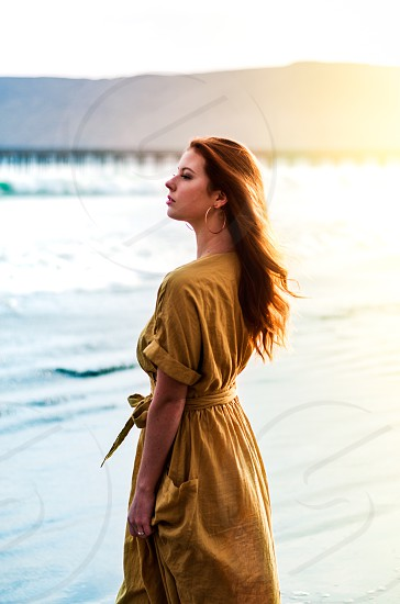 Model standing on beach during sunset. photo
