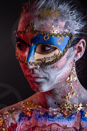 Portrait of a young masked woman with creative makeup on the theme of Venice Carnival photo