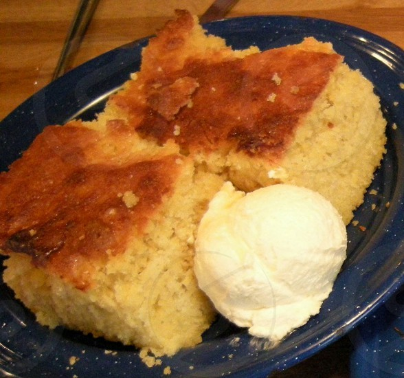 Cornbread with butter lump on blue speckle plate with wood background photo