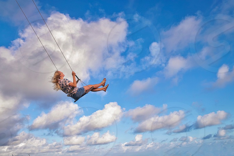 Swing girl sky clouds woman blonde summer travel  photo