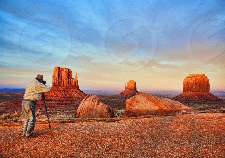Seen from behind a photographer uses his tripod to photograph Monument Valley at sunset photo