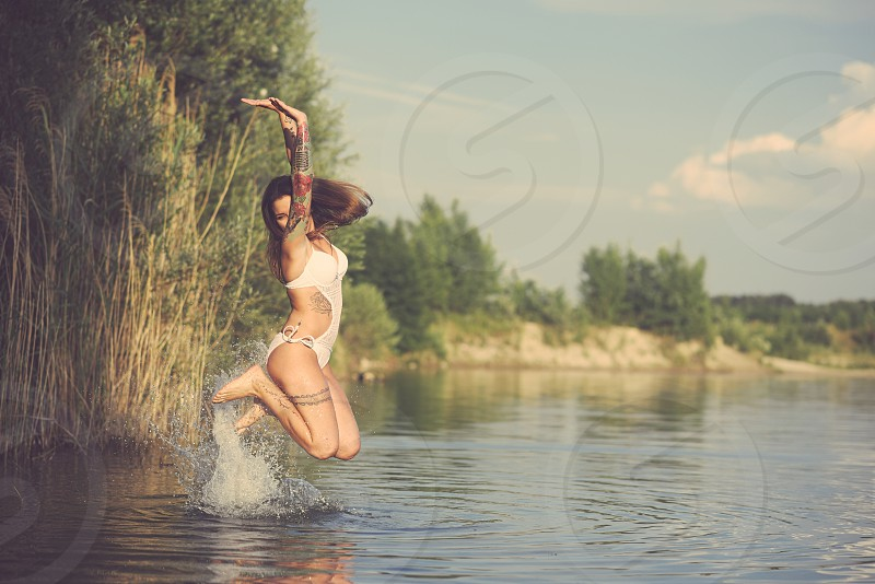 Young Tattooed Woman Jumping from Lake Water on a Summer Day photo