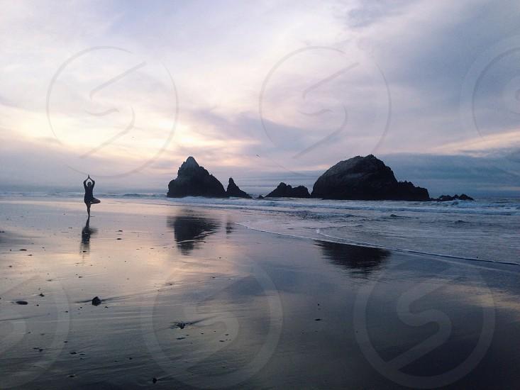 person doing yoga on the seashore photo