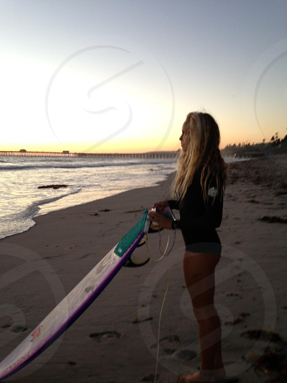 woman in black rash guard holding purple surfboard on sea side under clear sky photo