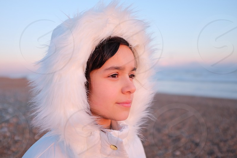 Portrait of young dark haired girl in a white fluffy hooded winter coat on a beach looking out to sea to the right of the frame with a thoughtful expression photo