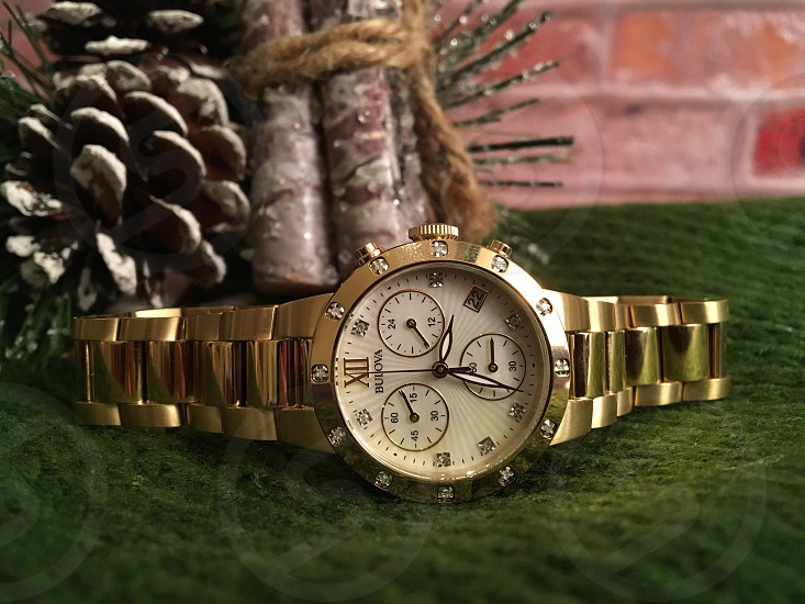 tilt shift photography of gold link band round face chronograph watch on green fabric textile beside christmas ornament photo