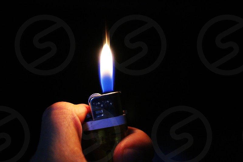 hand holding lighter with flame in darkness photo